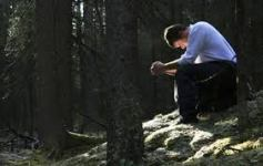 man in woods praying